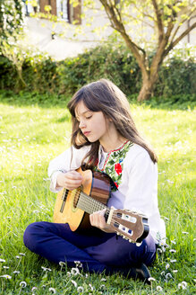 Girl sitting on a meadow playing guitar - LVF003224