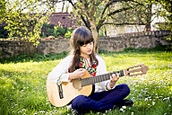 Girl sitting on a meadow playing guitar - LVF003227