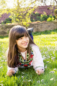 Portrait of smiling girl lying on a meadow - LVF003229