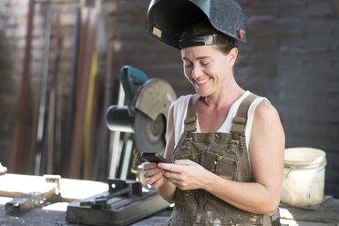 Female welder in metal workshop using mobile phone - ABAF001668
