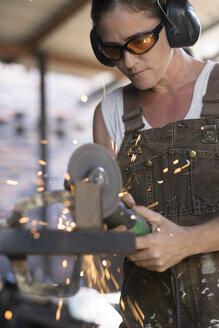 Female welder working in metal workshop - ABAF001672