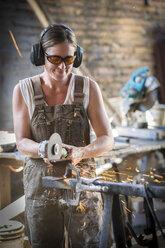 Female welder working in metal workshop - ABAF001670