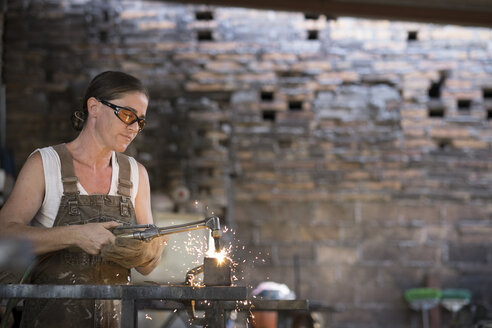 Female welder working in metal workshop - ABAF001675