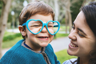 Portrait of little boy making faces with heart shaped glasses - GEMF000222
