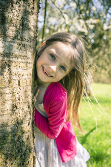 Portrait of smiling girl besides tree trunk - SARF001743