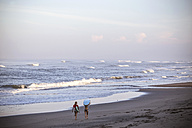 Indonesia, Bali, two women carrying surfboards on the beach - KNTF000004