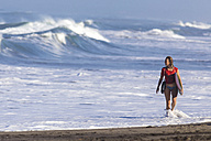 Indonesia, Bali, woman carrying surfboard at seafront - KNTF000006