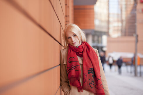 Portrait of young woman with red scarf leaning on wall - MMFF000831