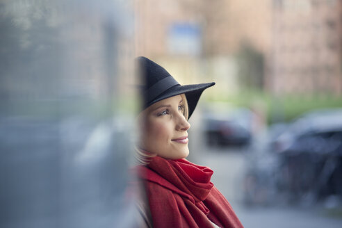 Portrait of smiling young woman wearing black hat and red scarf - MMFF000834