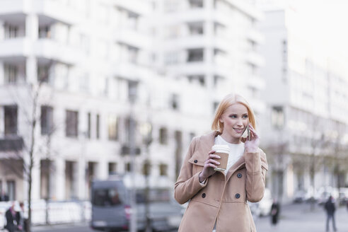 Germany, Berlin, young woman with coffee to go telephoning with smartphone - MMFF000842
