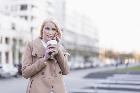 Germany, Berlin, young woman with coffee to go telephoning with smartphone - MMFF000843