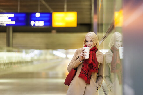 Young woman with coffee to go waiting in a station building - MMFF000841