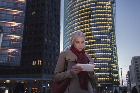 Germany, Berlin, young woman with mini tablet in the evening at Potsdam Square - MMFF000850