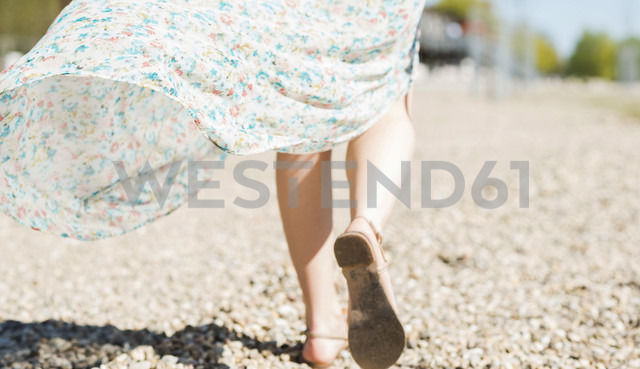 Woman walking on shingle beach - UUF003868