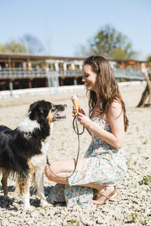 Young woman with dog and ice cream cone outdoors in summer - UUF003930