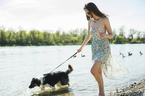 Germany, Mannheim, young woman walking with dog at River Rhine - UUF003932