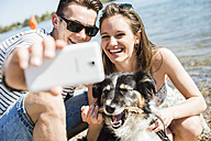 Happy young couple taking selfie with dog by the riverside - UUF003937
