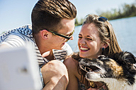 Happy young couple taking selfie with dog by the riverside - UUF003939