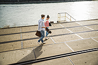 Young man and woman walking at track by the riverside - UUF003942
