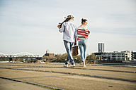 Young man and woman walking at track by the riverside - UUF003943