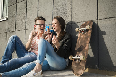 Happy young couple sitting on ground with headphones and skateboard - UUF003898