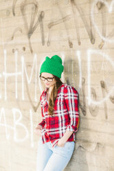 Young woman with checkered shirt and green wooly hat leaning at graffiti wall - UUF003908