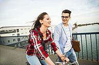 Germany, Mannheim, young man and woman with bicycle on bridge - UUF003912