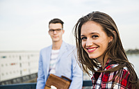 Smiling young woman with man in background - UUF003919