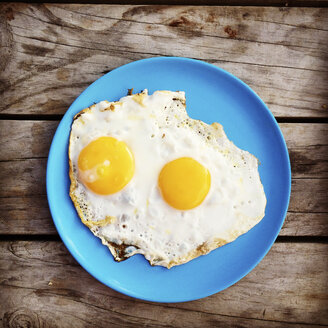 Breakfast, fried eggs sunny-side-up, wooden background - GWF003942