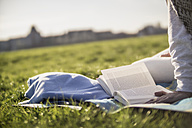 Close-up of woman reading book on blanket in meadow - RIBF000041