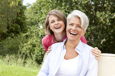 Laughing mother with adult daughter outdoors - MFRF000159