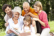 Happy extended family with book outdoors - MFRF000167
