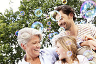 Happy grandmother, father and girl surrounded by soap bubbles - MFRF000170