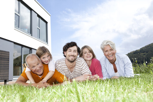 Portrait of happy extended family lying on lawn - MFRF000173