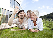 Happy grandmother, father and girl lying on lawn using cell phone - MFRF000176