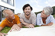 Happy adult son and parents lying on lawn with construction plan - MFRF000179