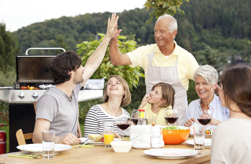 Adult son high fiving father at barbecue party - MFRF000205