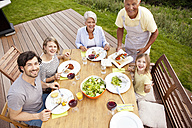 Grandfather serving food from barbecue grill for family at garden table - MFRF000183