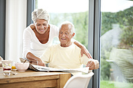 Mature couple reading newspaper at breakfast table - MFRF000208