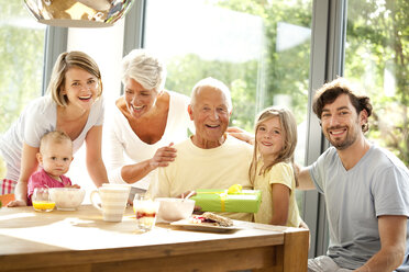 Portrait of happy extended family with present at breakfast table - MFRF000211