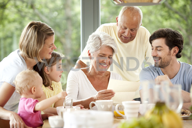 Happy granddaughter with her family reading letter at breakfast table - MFRF000214 - Michelle Fraikin/Westend61