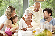 Happy granddaughter with her family reading letter at breakfast table - MFRF000214