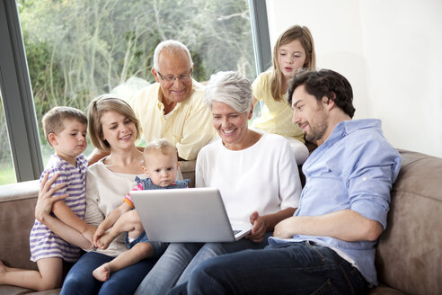 Extended family on couch using laptop - MFRF000223