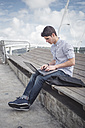 Spain, Ferrol, young man using a laptop outdoors - RAEF000147