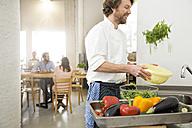 Cook of a little restaurant preparing lettuce in the kitchen - FKF001040