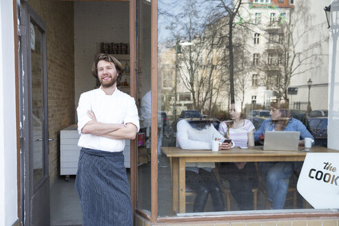 Germany, Berlin, owner and cook of a bistro standing at entrance door - FKF001056