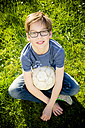 Portrait of boy sitting on a meadow with soccer ball - LVF003259