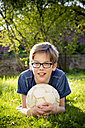 Portrait of boy lying on a meadow with soccer ball - LVF003258