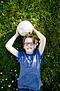 Portrait of boy lying on a meadow with soccer ball - LVF003256