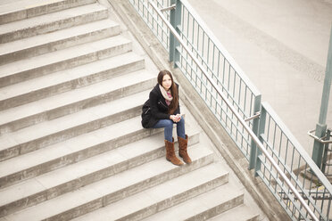 Young woman sitting on stairs - MMFF000705